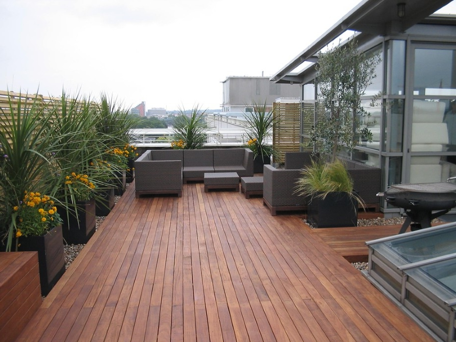 awesome rooftop garden with fascinating brown wicker seating area set on wooden deck floor. Black Bedroom Furniture Sets. Home Design Ideas
