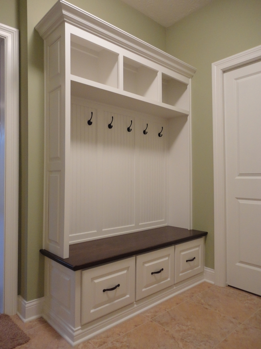 Soft brown wall paint color background paired with awesome Mudroom bench and hooks