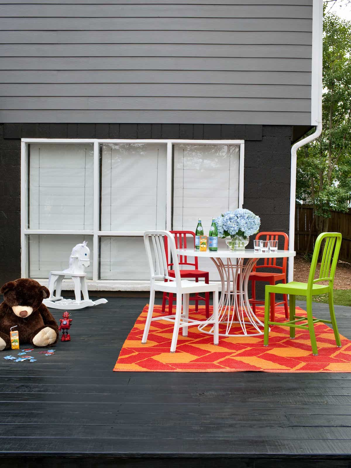 Cozy Black Deck With Red And Orange Patterned Outdoor Rug (Image 7 of 15)