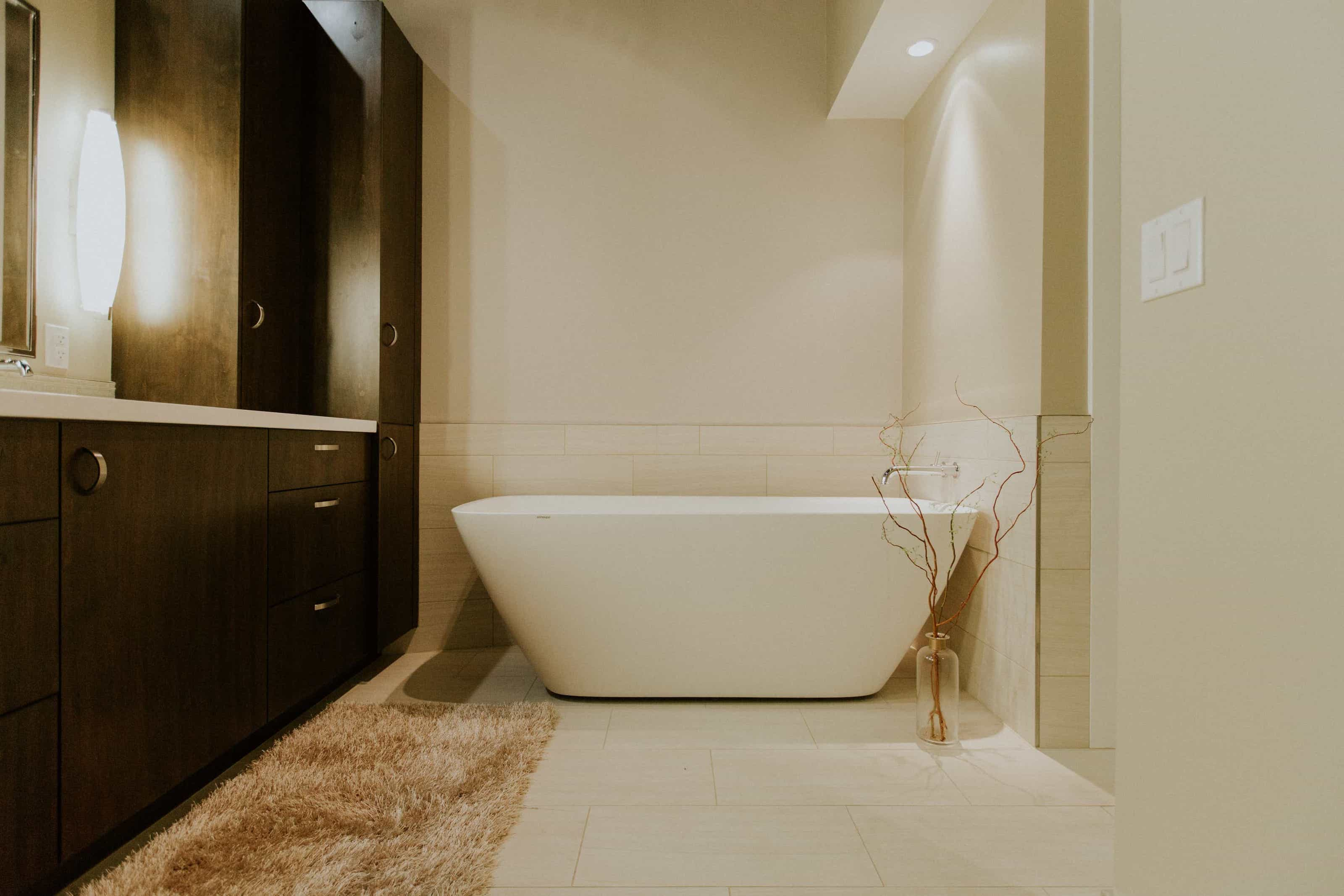 Modern Bathroom With White Bathtub, Large Built In Wood Vanity Cabinetry And Beige Shag Rug (Image 8 of 15)