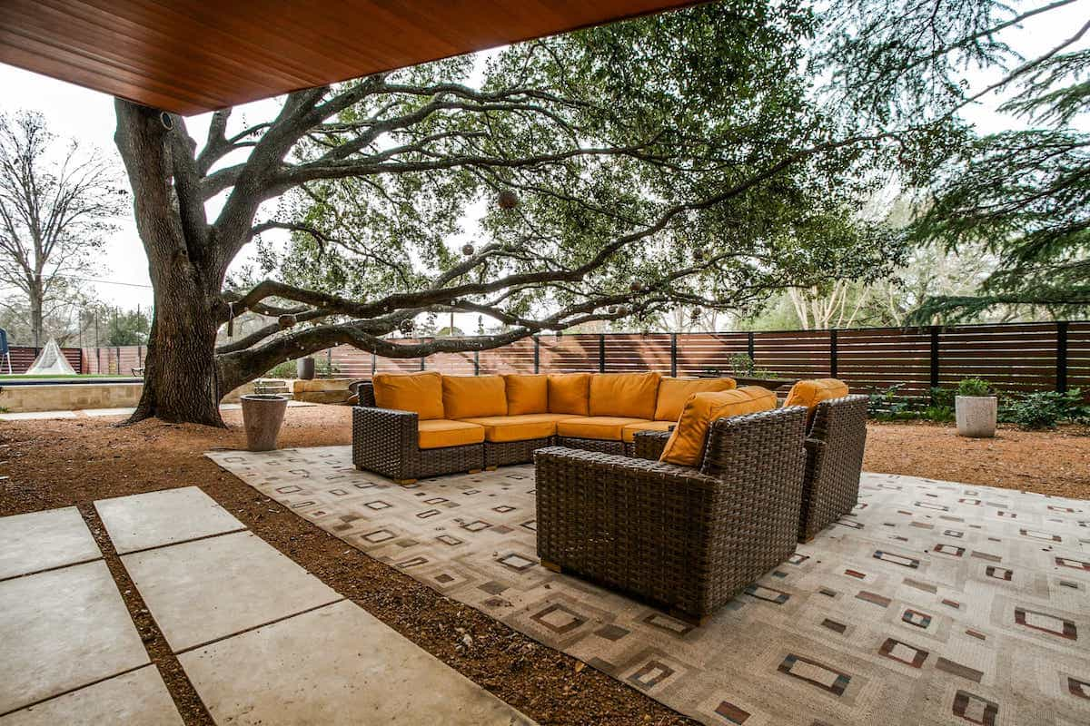 Outdoor Sitting Area With Wicker Furniture On Large Area Outdoor Rug (Image 14 of 15)