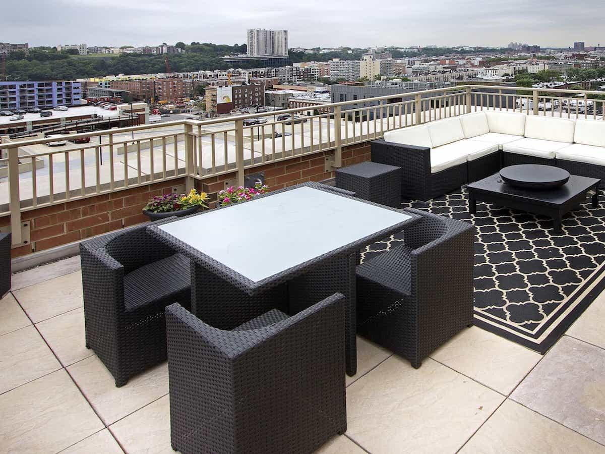 White Cushions And Dark Outdoor Rug Liven Up The Dark Wicker Patio Furniture Set On This Rooftop Outdoor Lounge (View 4 of 15)
