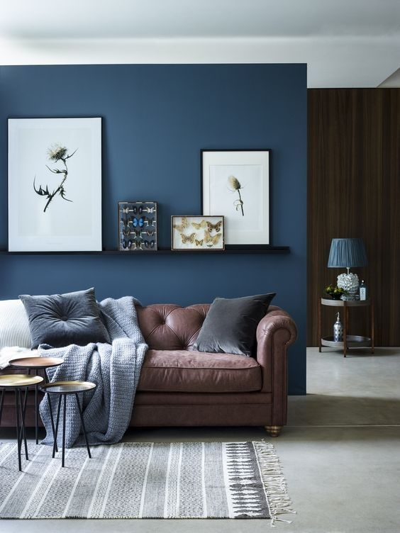 Chic Seating Area With A Brown Sofa And A Navy Accent Wall And Intended For Brown Furniture Wall Accents (Image 3 of 15)